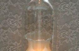 Świecznik z butelki z białym kwiatem