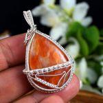 Kalcyt, srebrny wisior z kalcytem pomarańcz - srebrny wisior na dłoni z kalcytem