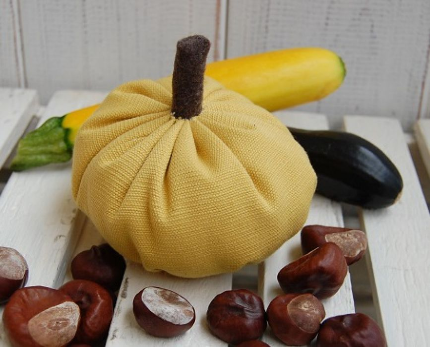 Mała, żółta dynia - jesienna dekoracja