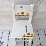 białe krzesełko z oparciem żyrafa