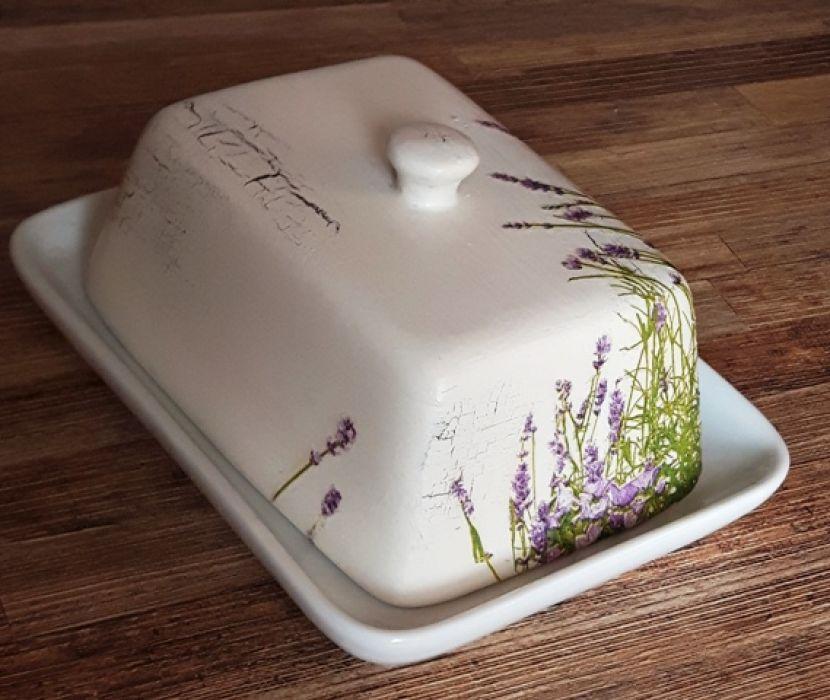 Maselnica lawendowa ecru - Kwiatki i trawy wraz z dzwoneczkami tworzą romantyczną łąkę okalającą maselniczkę u ich dołu z dwóch boków przyległych do siebie (dłuższy bok oraz krótszy). Maselnica także jest delikatnie zdobiona efektami postarzenia (tj. miejscami delikatne złuszczenia
